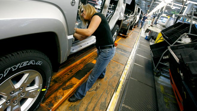 in a 2011 file photo, Pam Bialecki works on a 2012 Jeep Wrangler at the Chrysler Toledo Assembly complex, in Toledo, Ohio.