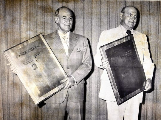 In this May 1972 photo, Andy Cohen, left, and Syd Cohen right, are shown holding engraved plaques honoring their careers during a testimonial dinner at the Sheraton Motor Inn.
