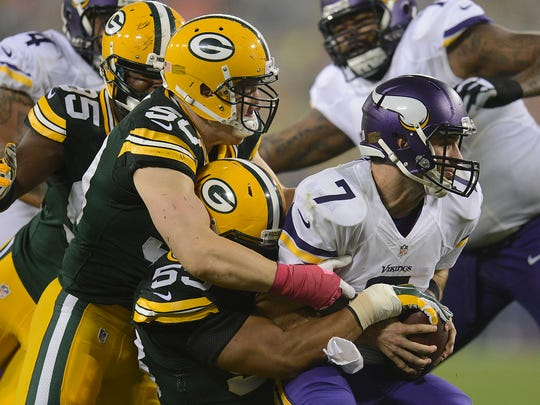 Green Bay Packers Nick Perry (53) and A.J. Hawk (50) sack quarterback Christian Ponder (7) against the Minnesota Vikings during Thursday night's game at Lambeau Field.
