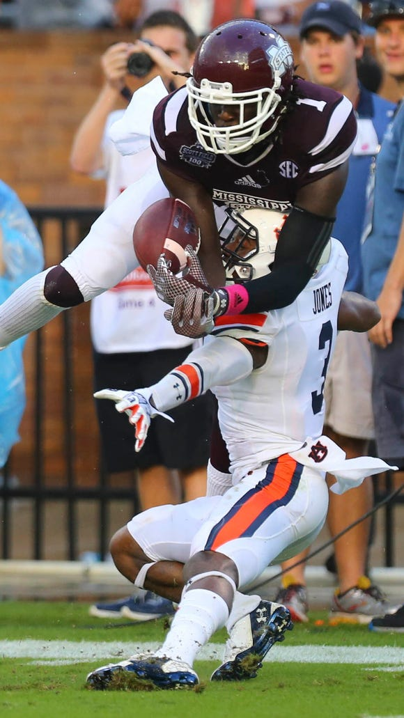 Mississippi State wide receiver De'Runnya Wilson reaches over Auburn cornerback Jonathan Jones for a pass on Saturday. Jones was called for pass interference on the play.