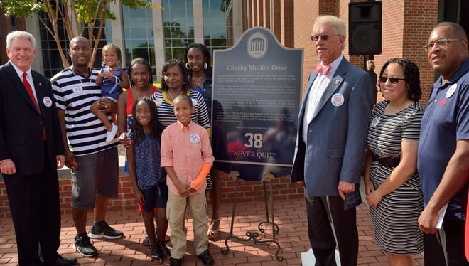 Chancellor Dan Jones, Carver Phillips and family, Coach Billy Brewer and Ole Miss AD Ross Bjork posed with the sign that will be posted along Chucky Mullins Drive.