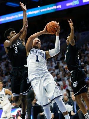 Villanova guard Jalen Brunson (1) takes a shot past Butler guard Kamar Baldwin (3) and guard Paul Jorgensen (5) during the first half of an NCAA college basketball game, Saturday, Feb. 10, 2018, in Philadelphia.