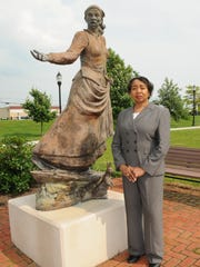 Clara Small stands next to the Harriet Tubman statue