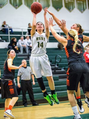 Iowa City West's Danielle Craig (14) shoots the ball as West Des Moines Valley's Emily Smith (21) defends during the first half of play in Iowa City on Saturday, January 24, 2015. Valley won the game 65-56.