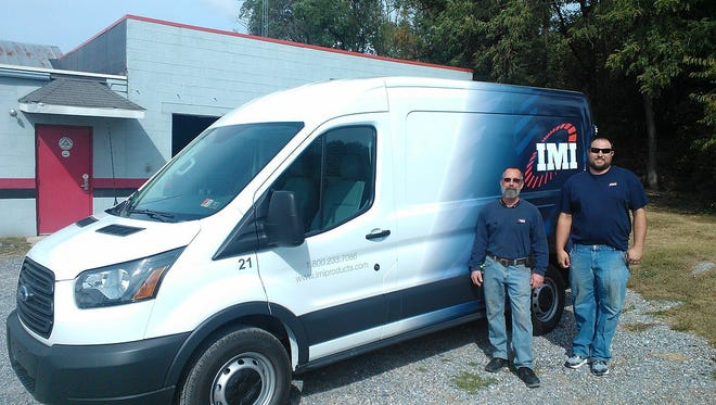 IMI service technicians Pat Durham, left, and Matt Singley stand with one of the company vans recently. The company recently announced its new location near the Chambersburg Mall.
