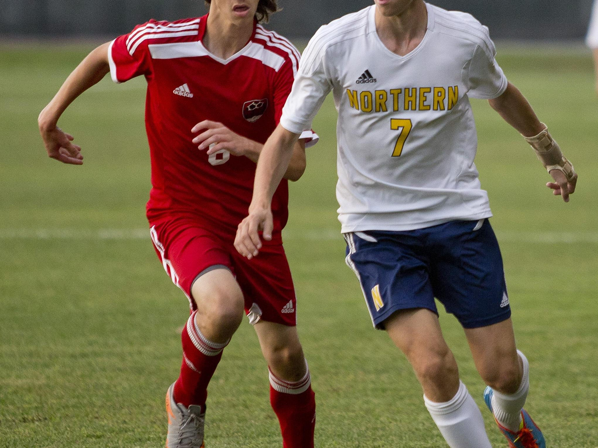 Port Huron Northern junior James Robertson works the ball in front of Port Huron senior Zach Bowen during a soccer game Thursday, September 24, 2015 at Port Huron Northern High School.