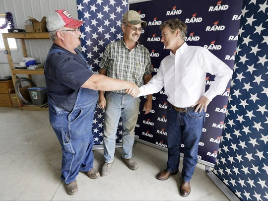 Republican presidential candidate, Sen. Rand Paul, R-Ky., talks with farmers John Vandee, left, and David Armstrong, both of Deep River, Iowa, during a campaign stop at the Craig Lang farm Thursday, July 2, 2015, in Brooklyn, Iowa.