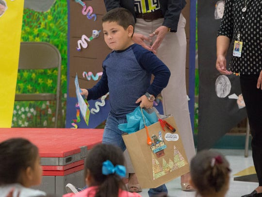 Kenton Scarborough, a first-grade student at University Hills, receives his prize for having read more minutes than any other first grade student during the Scholastic Summer Reading Challenge. Wedensday October 18, 2017. University Hills was named New Mexico's top school for the second year in a row for the reading challenge. Caption Override