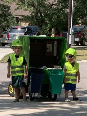 Georgetown brothers Hendrik, left, and Alarik Anderson stand ready with the toy garbage truck their mother and grandfather built for them for Halloween.