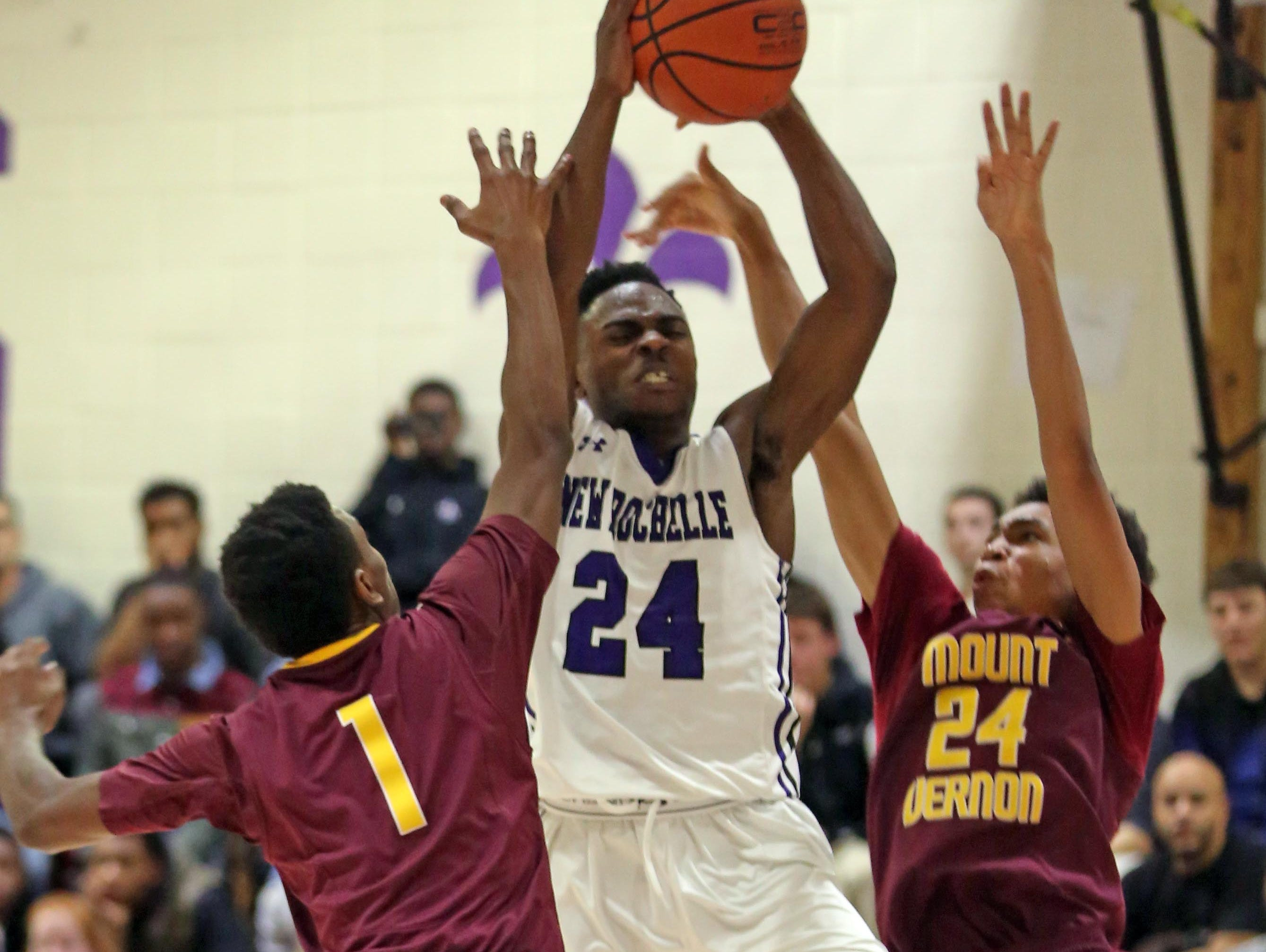 Jamel Wallace (24) of New Rochelle gets his shot block by Jared Young (1) and Jasen Stanley (24) of Mount Vernon during game action at New Rochelle High School on Jan 4, 2016. Mount Vernon defeated New Rochelle 72-63.