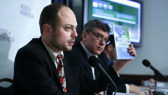 """Vladimir Kara-Murza, senior policy adviser at the Institute of Modern Russia, holds up a copy of the report on """"Winter Olympics in the Sub-Tropics"""" as Russian opposition leader and former Deputy Prime Minister Boris Nemtsov listens during a news conference on """"Corruption and Abuse in Sochi Olympics"""" at the National Press Club in Washington, DC.  Jan. 30, 2014 ."""
