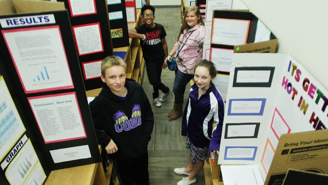 During Friday's science fair at Cobb Middle School, a group of seventh-graders pose near their projects.