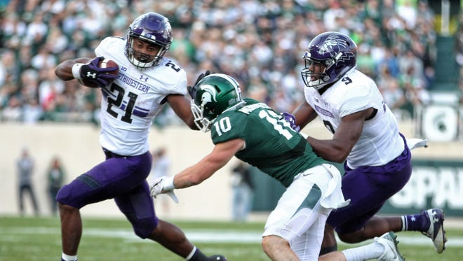 Northwestern Wildcats running back Justin Jackson (21) runs the ball against Michigan State Spartans safety Matt Morrissey (10) during the second half of a game at Spartan Stadium in 2016.