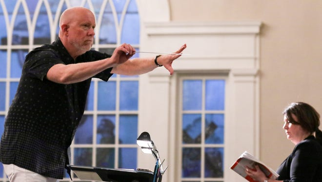 """Don Campbell, left, conducts near soloist Kristen Wunderlich, right, during practice with the GAMAC Chorale and Chamber Orchestra and the Southern Wesleyan University Concert Choir at Boulevard Baptist Church in Anderson on Tuesday. The group plays """"An Opera in Disguise: Verdi's 'Requiem'"""" on Friday."""