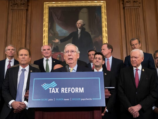 Senate Majority Leader Mitch McConnell, center, was among the Republican congressional leaders who developed and approved a tax plan that goes into effect in 2018.