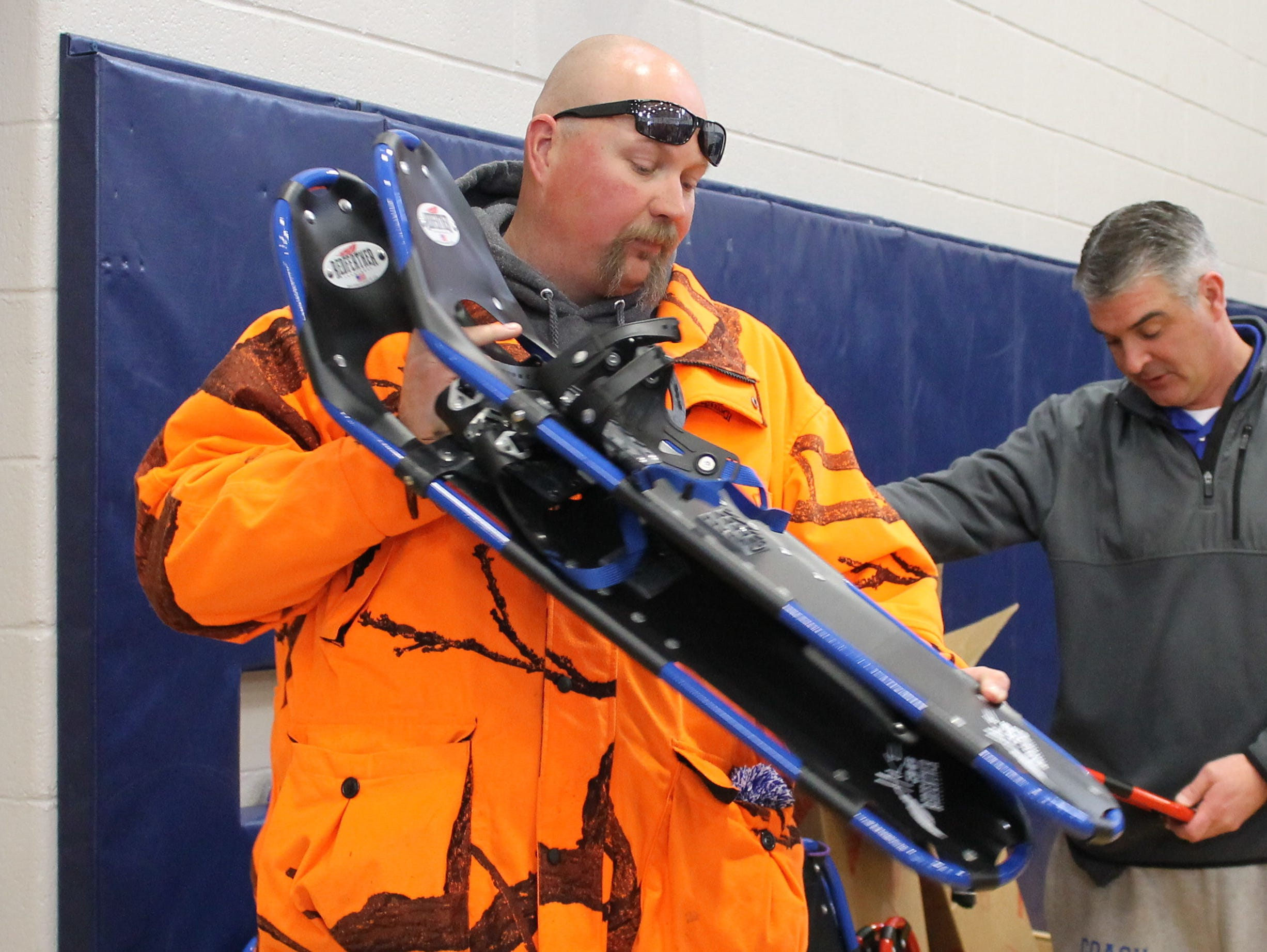 Millbrook High School teacher Shawn Stoliker, center, inspects a snowshoe for student use within the school's gym.