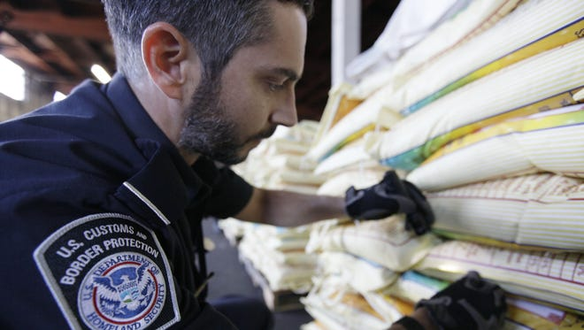 A 2011 photo of agriculture specialist Mark Murphy, with U.S. Customs and Border Protection, examining bags of rice in Oakland, Calif.