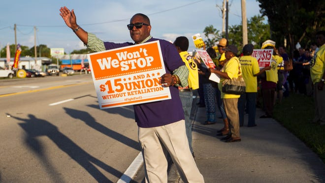 Larry Aguilar joins workers asking for a living wage of $15 an hour and a union on Pondella Road on Tuesday in North Fort Myers.