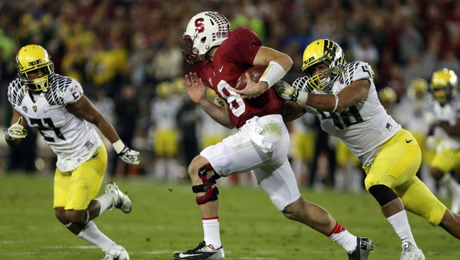 Stanford quarterback Kevin Hogan (8) tries to elude Oregon linebacker Rodney Hardrick (48) during the second quarter of the Cardinal's victory Thursday at Stanford Stadium.