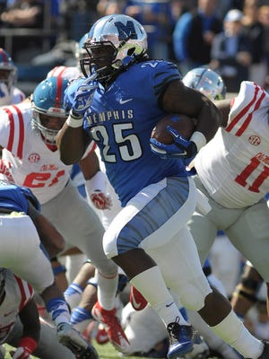Memphis Tigers running back Jarvis Cooper (25) carries the ball against Mississippi Rebels defensive end Channing Ward (11) during the game at Liberty Bowl Memorial Stadium.