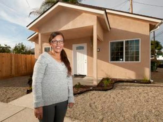 Adelfa Tinoco poses in front of her new home on Tuesday, November 18, 2014. Tinoco was the beneficiary of a 30-year $120,000 loan at 0 percent interest, which permitted the construction of a new home. Self-Help Enterprises oversaw the construction of a two bedroom, one bathroom 494-square foot house with a 60-square foot porch that was built on the existing lot. A little over a year after losing her home to a fire and relocating to Porterville with family, Tinoco along with her son and daughter will enjoy the holidays in her new, safe and affordable home.