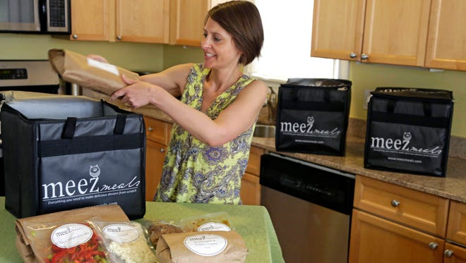 Jen Collins Moore, owner of Meez Meals, places some of her ready to cook meals in a delivery container in her kitchen in Chicago.
