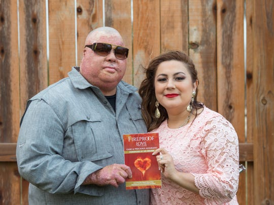 """Gabe and Precious Alvarado display their book """"Fireproof Love: Surviving the Heart-Wrenching Experience of an Industrial Accident."""" Gabe Alvarado was severely burned and lost an arm in a Corpus Christi refinery fire in July 2009."""