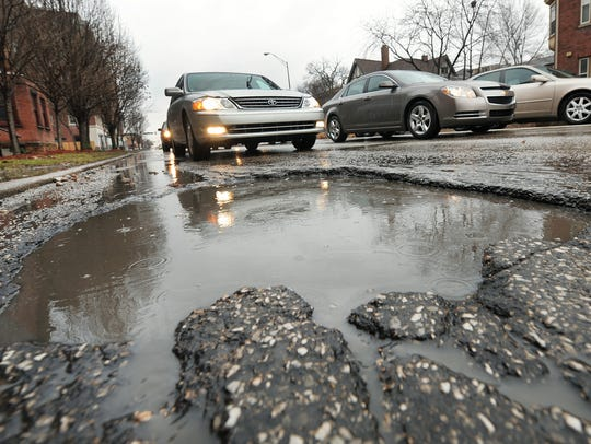 A gigantic pothole about 12 inches deep is filled with