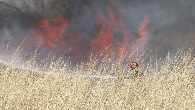 An Alamogordo firefighter stands in front of heavy grass while extinguishing Monday's grass fire in the area behind the Texas New Mexico power station.
