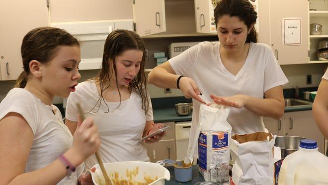 Three members of the Cupcake Cuties whip up their winning cupcakes.