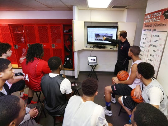 Park Tudor coach Kyle Cox uses analytics showing play-by-play notations (on left of screen) as he goes over game video with players, Jan. 22, 2015.
