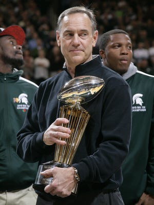 Michigan State football coach Mark Dantonio holds the 100th Rose Bowl championship trophy Jan. 7, 2014, in East Lansing.