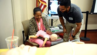 """Daniela, 9 of Hackensack, laughs as Giuseppe Defenza instructs her to hit the baby hard on the back to dislodge anything in it's airway. Defenza, a staff member of the simulation center at Holy Name Medical Center, taught attendees how to safely administer CPR during the  """"Familia y Salud"""" health fair on Saturday, October 21, 2017."""