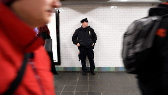 A NYPD officer surveys the corridor where Akayed Ullah allegedly detonated a pipe bomb on Monday. The rush-hour commute beneath the Port Authority Bus Terminal was largely back to normal on Tuesday.
