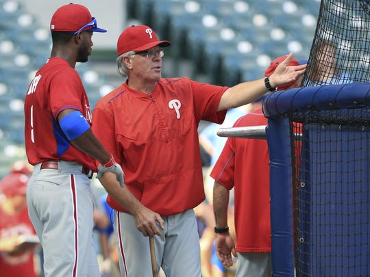 Interim Phillies manager Pete Mackanin talks with Domonic Brown #9 during warm ups before an Aug. 15 game against the Milwaukee Brewers. Mackinin had the interim title removed Tuesday and will manage the team next year, with an option for 2017.