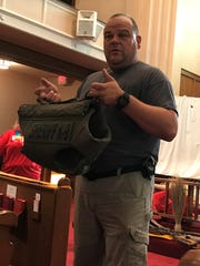 Det. Dave Stone shows a bullet and stab proof vest K-9 officers wear in dangerous situations to students and volunteers Thursday at a Vacation Bible School at Grace United Methodist Church.
