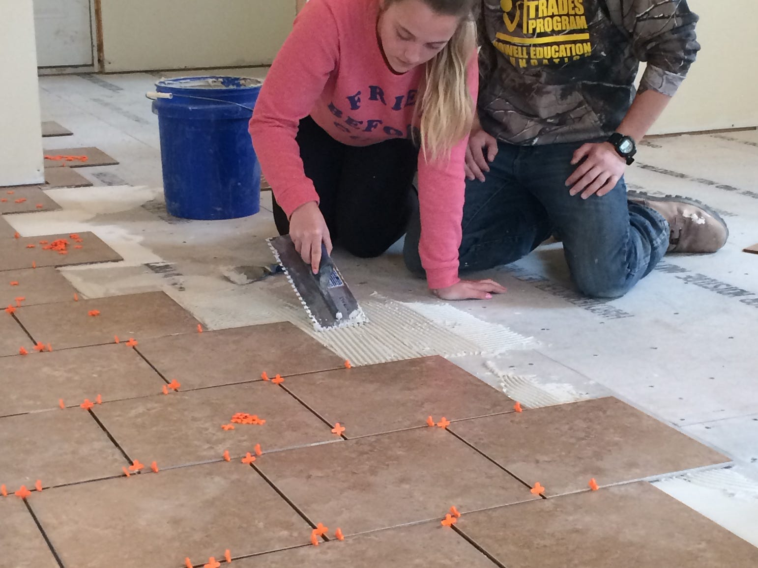 Whitmore Lake senior Jamie Gimson and Howell High School senior Sam Wallace place tiles down in a house they are building as part of a countywide Construction Trade Program high school students are able to participate in.