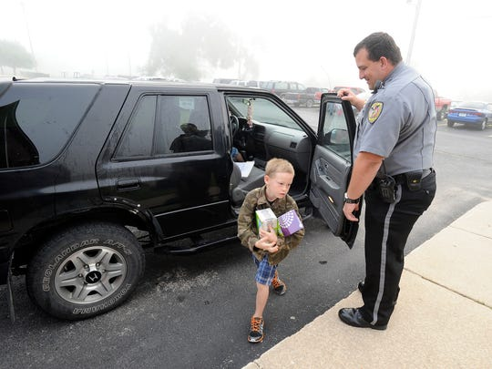 Cotter school resource officer Eddie Elliott welcomes a student to the first day of school last year.