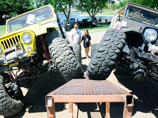 Roger Lee of Las Cruces and his daughter Laurel look at two Jeeps  during  a recent  Kiwanis Kars for Kids at Young Park. The event helps to raise money for scholarships and features antique, classic and custom cars and motorcycles.