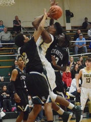 Holy Savior Menard's Jourdain Dishmond muscles his way through two Avoyelles Charter defenders during a game last year.
