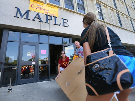 "Lori McKim helps daughter Morgan of Boone move into Maple Hall at Iowa State University Tuesday. Classes begin on Monday. Also helping is Morgan's brother Kyle. ""I've been crying all day,"" Lori confessed. <252>"