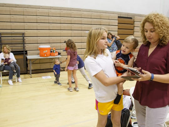 Electra Viveros gets ready before coaching a basketball game with help watching her three boys from friends, her mother, Bree Viveros, and her mother-in-law, Connie Kessler, Feb. 10, 2017.