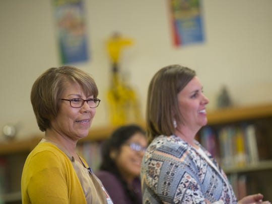 Shawl Iron Moccasin, left, assistant director of Indian education with the Farmington Municipal School District, and Apache Elementary School Principal Jennifer Bowles meet with parents on Monday in the school's library in Farmington.