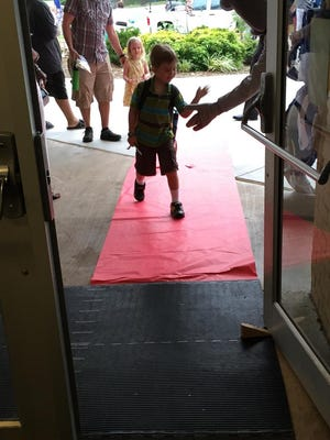 """First-grader Riley Bartholic walks the """"red carpet"""" outside Hall Fletcher Elementary School. Students returned to class Thursday."""