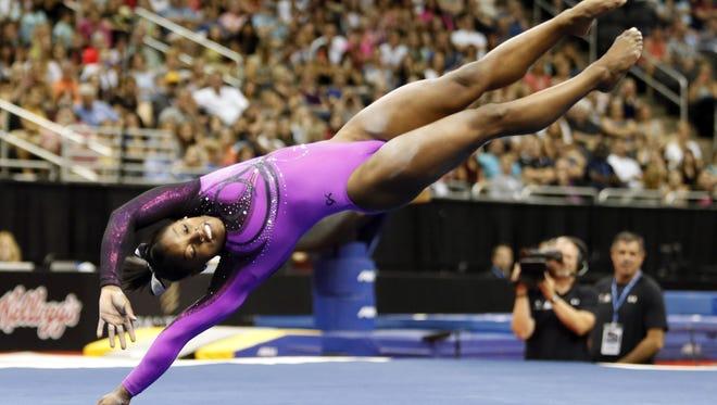 U.S. gymnastics champ Simone Biles smiles even as she goes upside down on the floor exercise.,