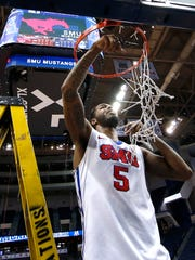 Southern Methodist Mustangs guard Nic Moore (11) cuts down the net after defeating the Connecticut Huskies during the final round of the American Conference Tournament at XL Center.