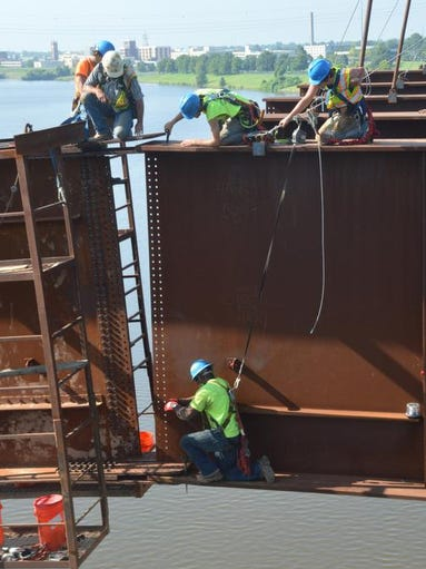 ANI Bridge Construction  Workers with Jensen Construction, a contractor from Des Moines, Iowa, place one of eight girders across the Red River as they construct the new Curtis-Coleman Memorial Bridge Friday, July 25, 2014. The girder is actually two girders bolted together. This girder is 205 feet wide and weighs over 150,000 pounds or 75 tons. Eight of those girders are set to be placed across the river. Pan American Engineers is the local company overseeing the construction of the new bridge for the Louisiana Department of Transportation and Development. The new bridge will replace the O.K. Allen Bridge.