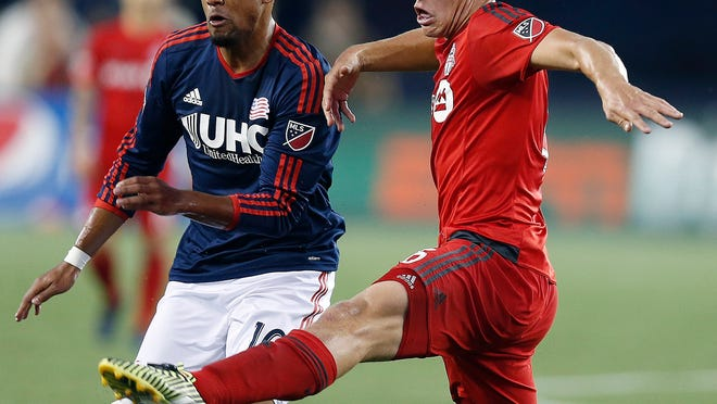 New England Revolution's Teal Bunbury, left, and Toronto FC's Nick Hagglund, right, vie for the ball during the first half of an MLS soccer game in Foxborough, Mass., Saturday, May 16, 2015. (AP Photo/Michael Dwyer)