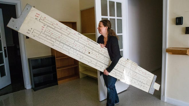 Tiffany Warmowski, chair of the History and Museum Committee for the MacMurray Foundation and Alumni Association, carries a giant slide rule out of a classroom at MacMurray Hall Thursday, Oct. 8, 2020. Warmowski was gathering items from the shuttered college to be preserved and exhibited by the Jacksonville Area Museum.