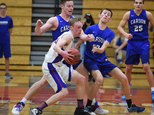 Reno's Drew Rippingham is double-teamed by Carson's Tez Allen left, and Trent Robison during Tuesday's playoff game at Reno High School